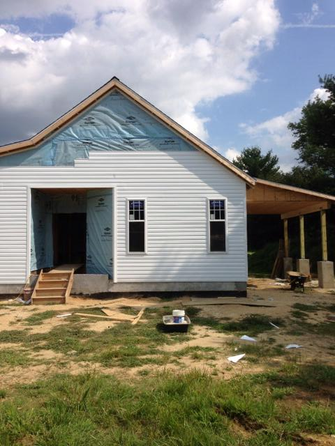 House under construction with white siding partially completed