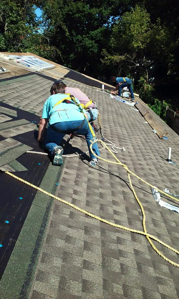 People installing roof shingles