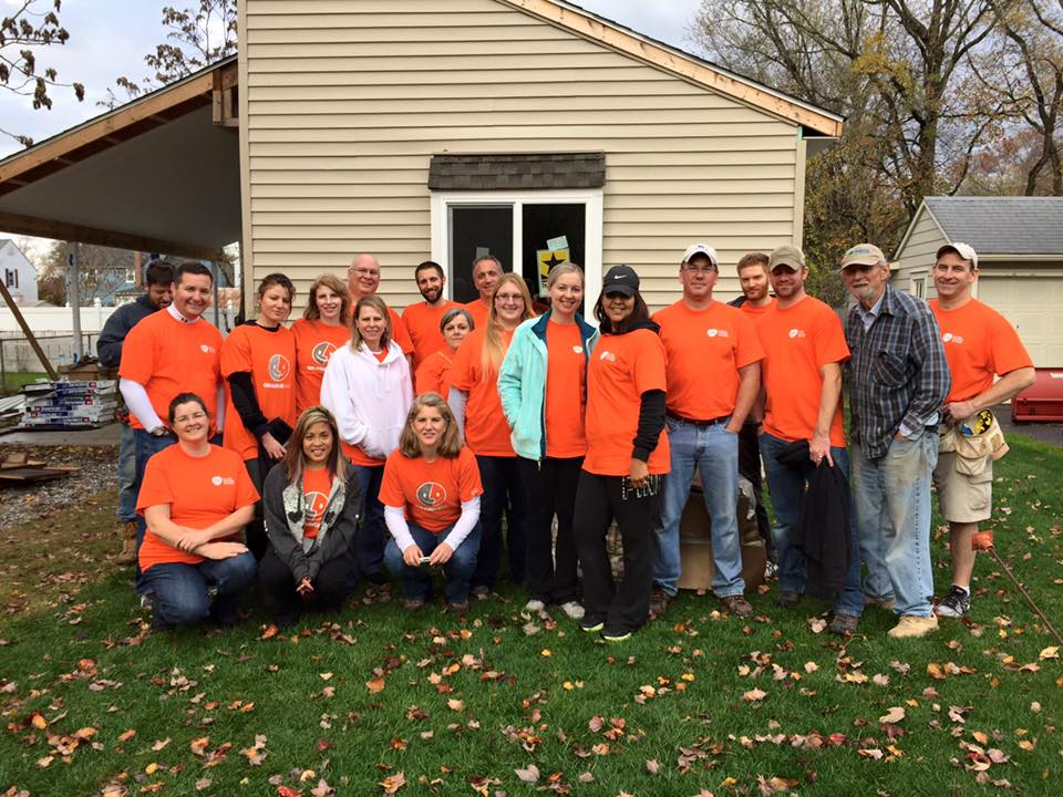 Volunteers wearing orange shirts standing in front of building