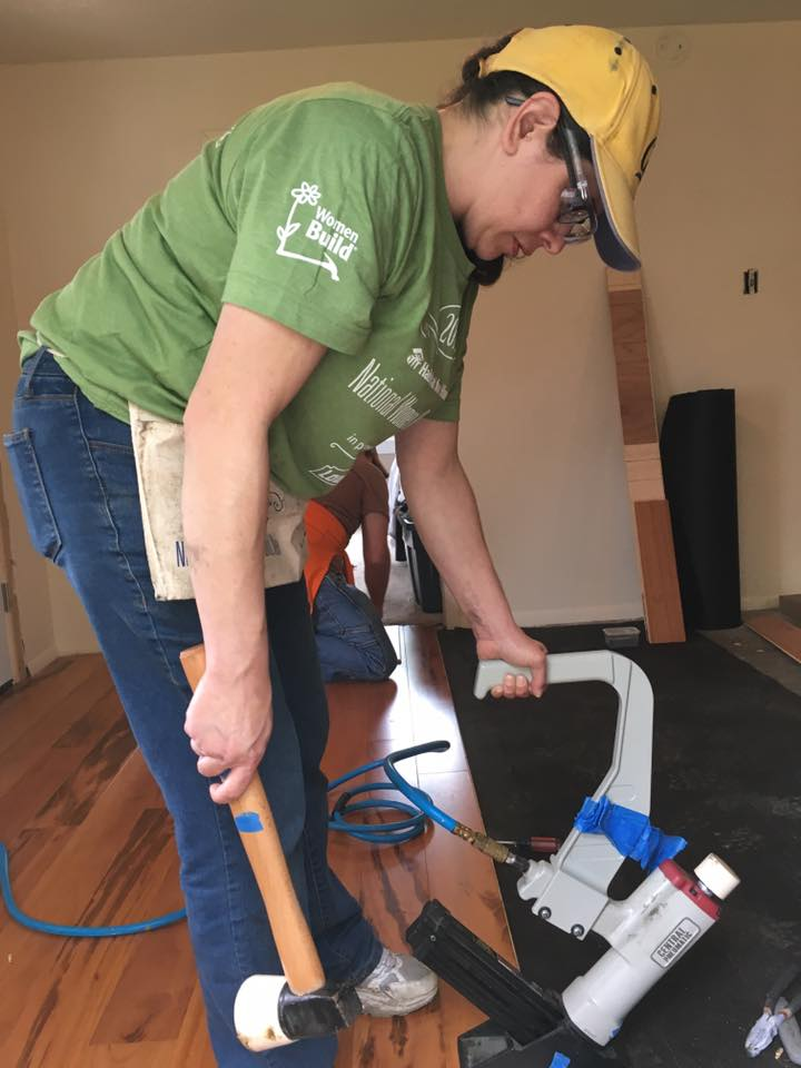Woman using tools to lay down new wood flooring