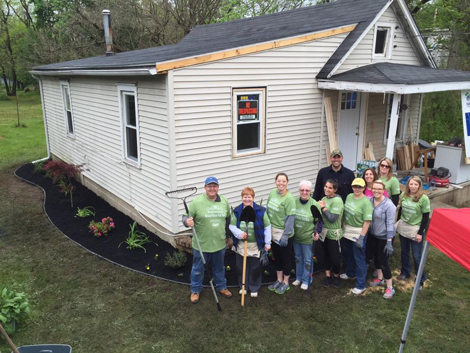 Volunteers proudly standing in front of home nearing completion