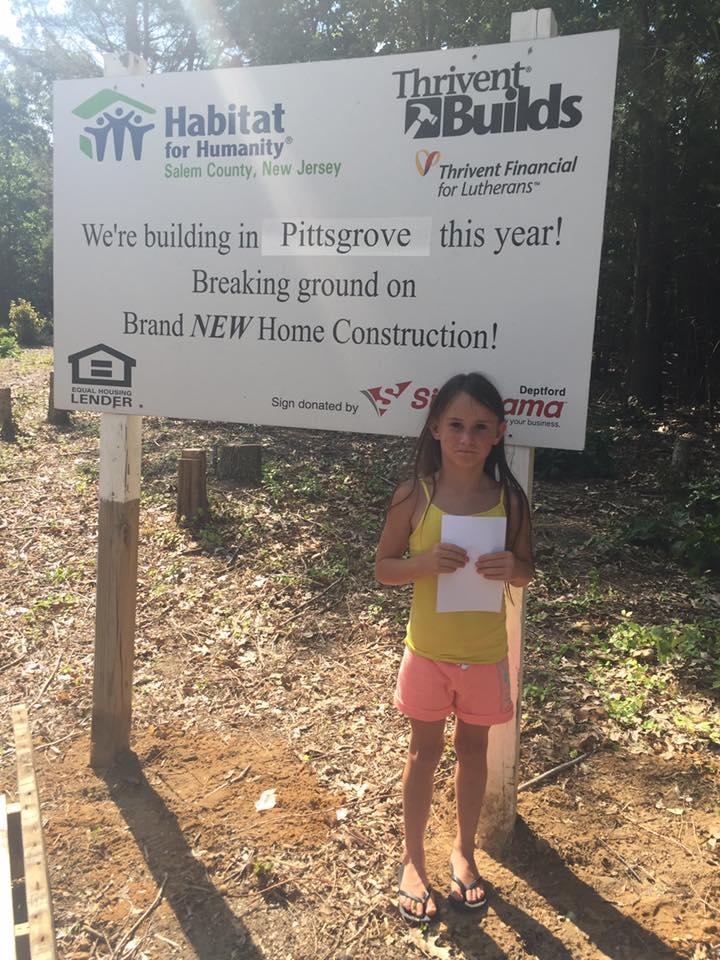 Little girl standing in front of Habitat sign