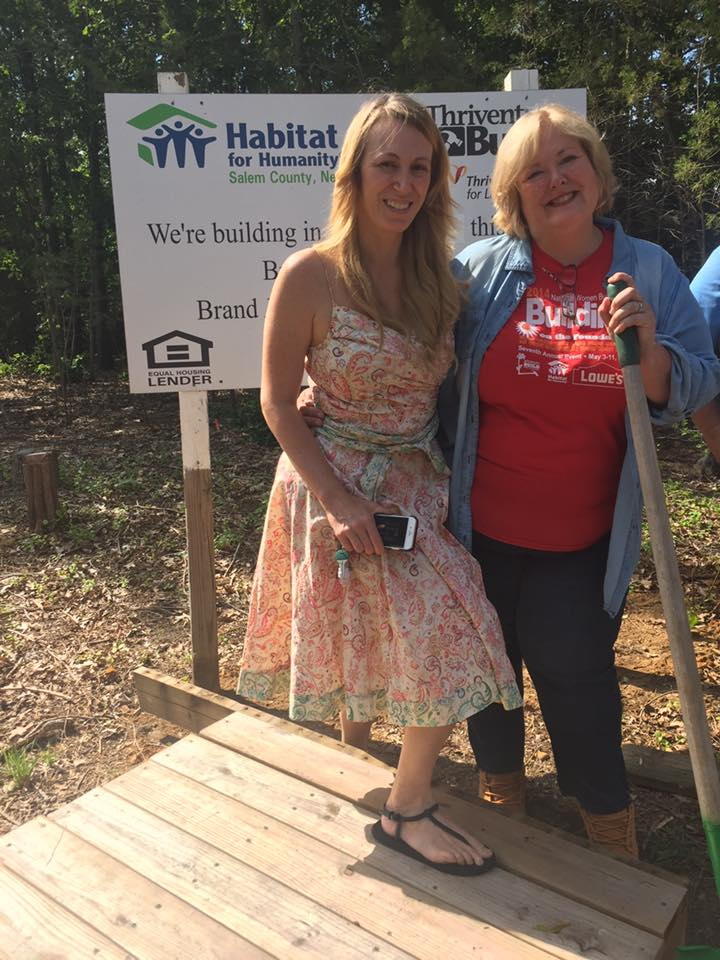 Two woman standing in front of habitat sign