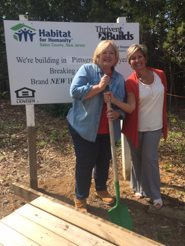 Two women smiling and holding shovel in front of sign