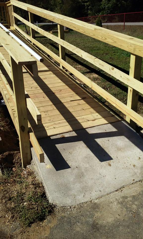 Wheelchair ramp with concrete footer attaching to sidewalk