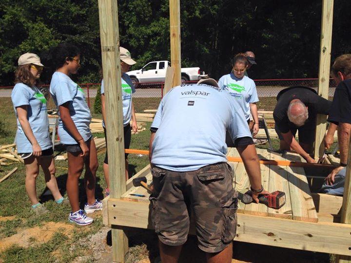 Volunteers standing around wooden structure