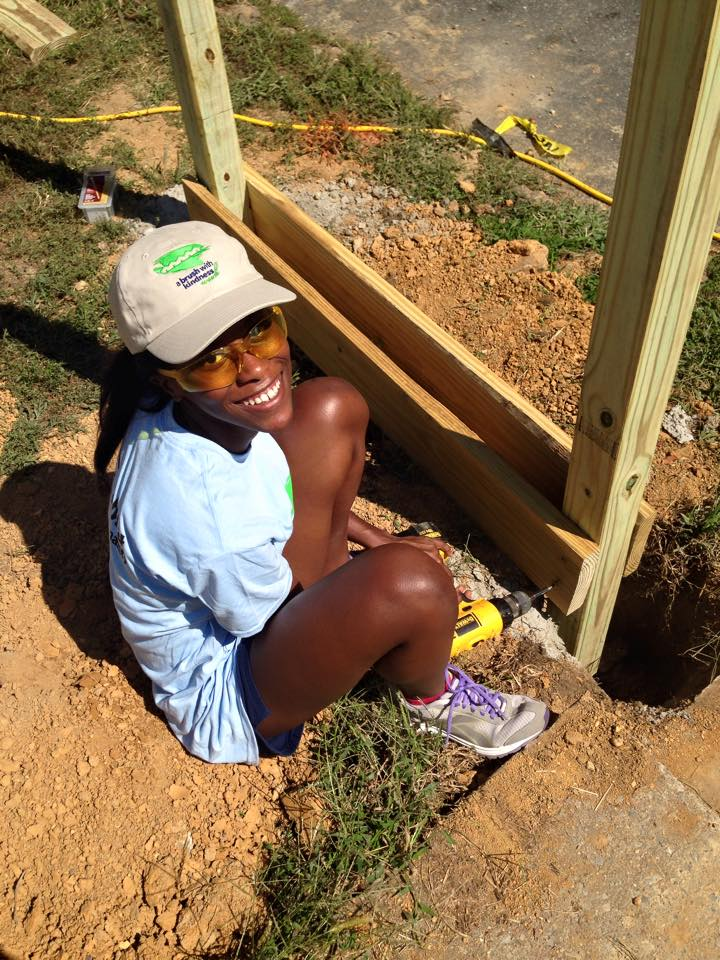 Volunteer sitting on ground and smiling at camera