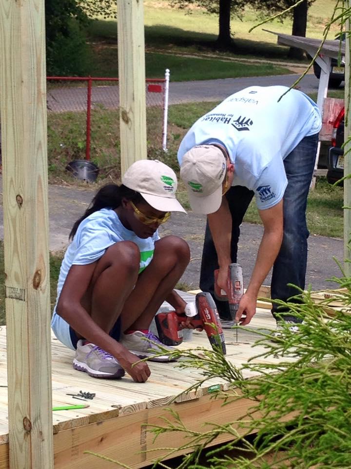 Two volunteers drilling in wood ramp