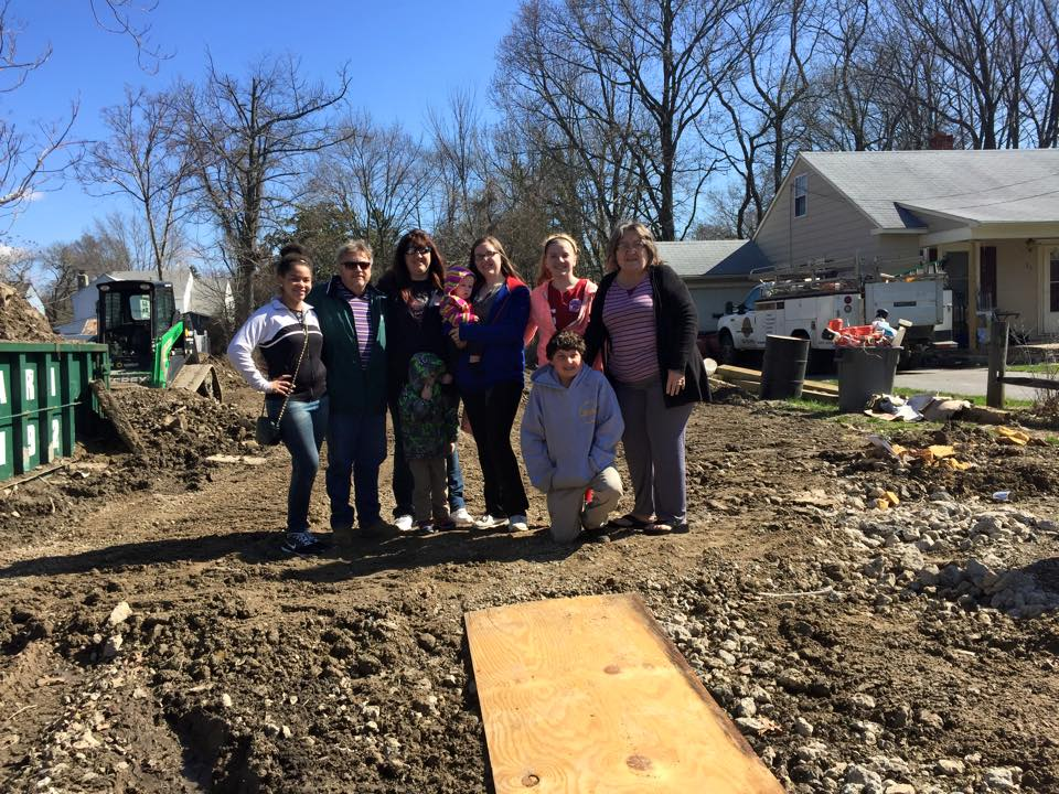 Group posing in dirt lot