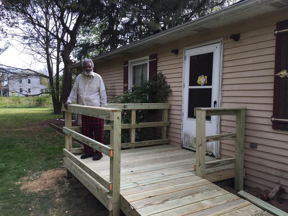 Older man standing on a new wheelchair ramp for his house