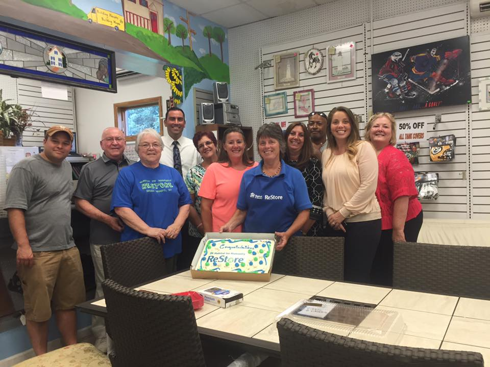 Group inside of Restore office showing off a congratulations cake