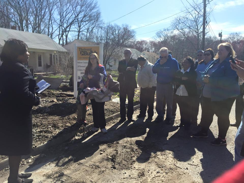 Group standing on newly broken ground for home