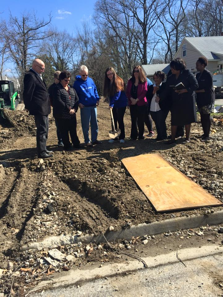 Group breaking ground on home wih woman using shovel