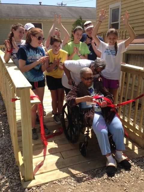 Group standing on new handicap ramp with woman in wheelchair cutting ribbon