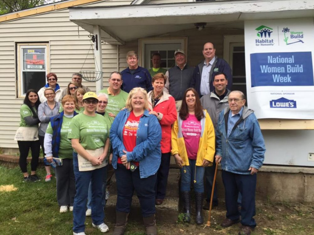 Group of volunteers and county commissioners in front of home