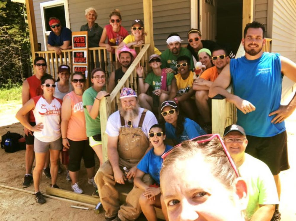 Goup of smiling volunteers standing on and around porch of newly completed home