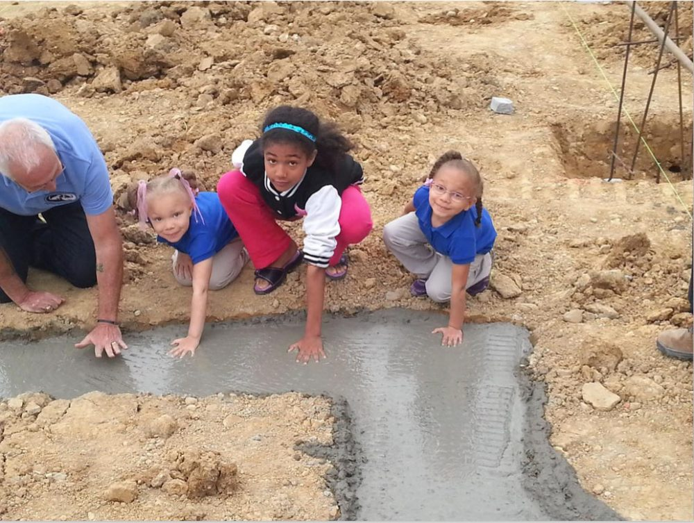 Children smiling at camera as they press their handprints into concrete foundation