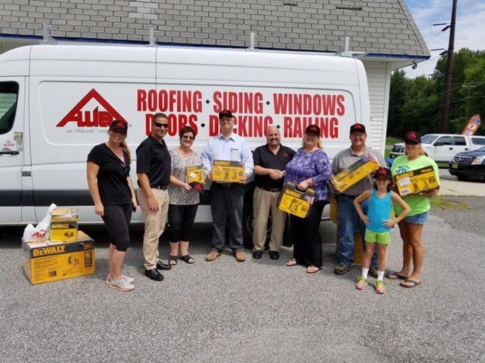 Volunteers standing in fron of construction company van