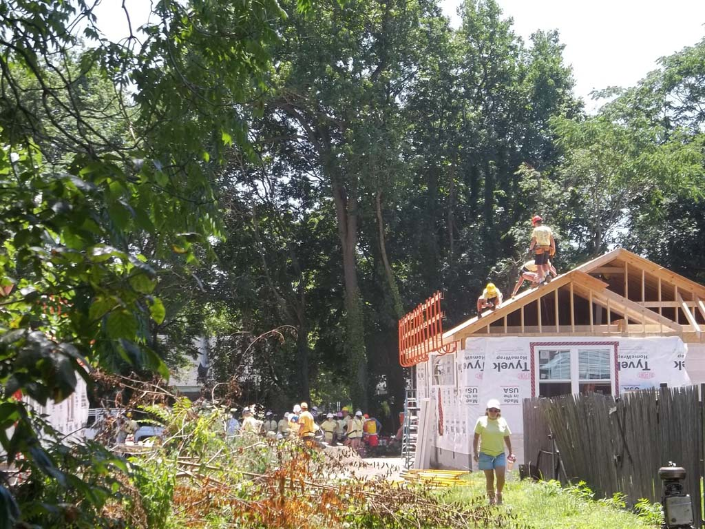 Volunteers working on roof with trees in background