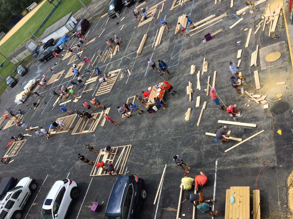 View from above showing people in parkng lots using wood to build frames